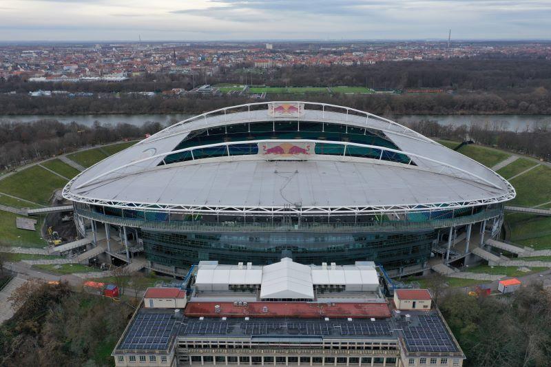 Das Stadion in Leipzig aus der Luft. Im Vordergrund ein gründerzeitliches Gebäude mit Solarpaneelen auf dem Dach.