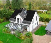 Blick auf ein freistehendes Einfamilienhaus mit Schrägdach, auf dem schwarze Module installiert sind.