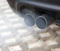 Zu sehen ist ein Auto-Auspuff, das Kohlendioxid das er ausstößt, soll durch Abscheidung von Kohlendioxid aus der Luft wieder eingefangen werden.