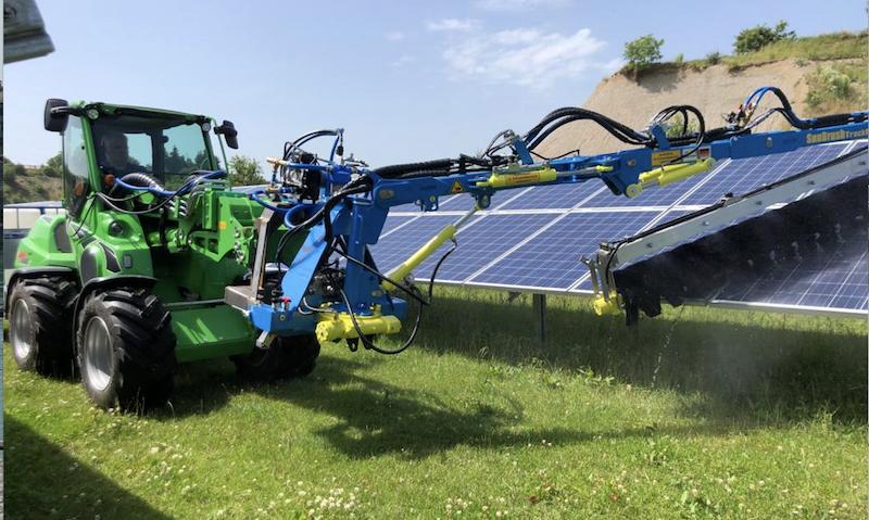 Reinigung von Photovoltaik-Anlagen: ein Fahrzeug fährt mit einer großen Bürste über eine Modulreihe.