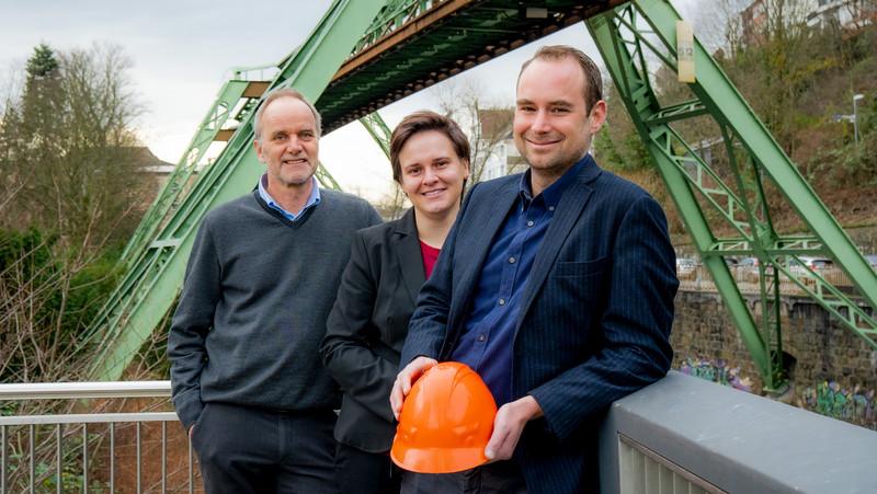 Drei Wiisenschaftler vor einer Stelze der Wuppertaler Schwebebahn