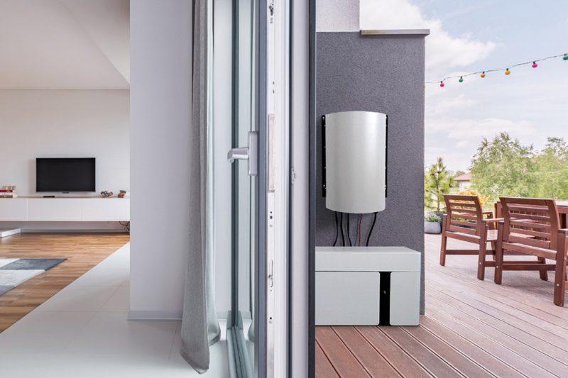 Blick auf Wohnzimmer und Terasse eines Hauses; an der Außenwand ist ein Stromspeichersystem angebracht;