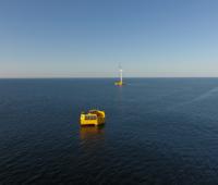Blick übers Meer, ein gelbes Boot und ein Offshore-Windrad