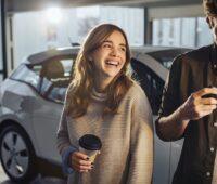 Zu sehen sind zwei Menschen mit einem E-Auto im Hintergrund, die die Senec.Cloud to go nutzen könnten.