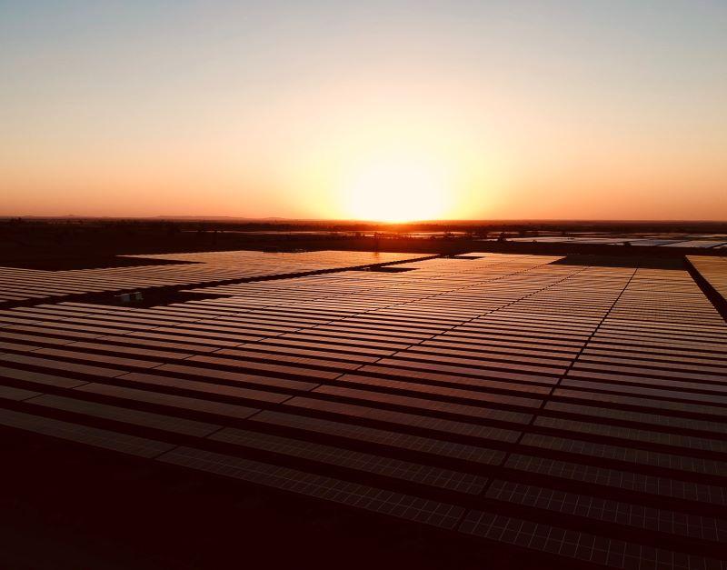 Sonnenuntergang über einem in rotes Licht getauchten Solarpark