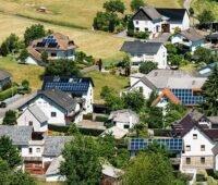 Zu sehen ist ein Dorf mit Photovoltaik-Anlagen, die im Sonnenschein stehen und nicht von Hochwasser betroffen sind.