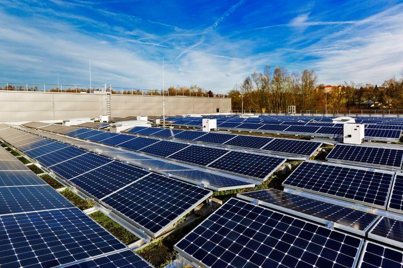 Blick auf eine Dach mit Solarmodulen und Wechselrichterboxen.