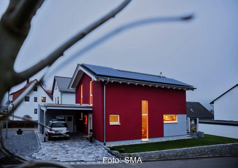 Ein beleuchtetes Haus mit Solaranlage auf dem Dach und einem Auto unter Carport.