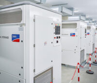 In einem Raum stehen mehrere Einheiten, die wie eine Art Metallschrank aussehen. Sie beinhalten Speichersysteme.