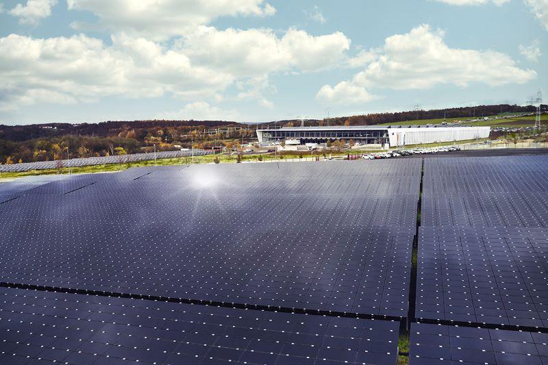 Eine Freiflächen-Solaranlage, auf der die Sonne reflektiert, vor einem Werksgelände.