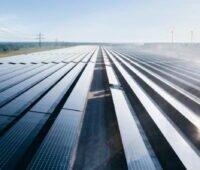 Eine Reihe von Solarstromanlagen zwischen zwei Hochspannungsmasten.