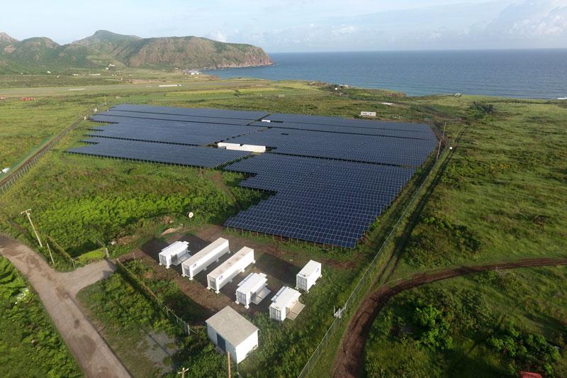 Luftaufnahe Solarpark mit Technik-Containern - Hintergrund: Karibische See