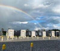 Eine Reihe von Containern mit Batteriespeichern vor wolkigem Himmel mit Regenbogen.