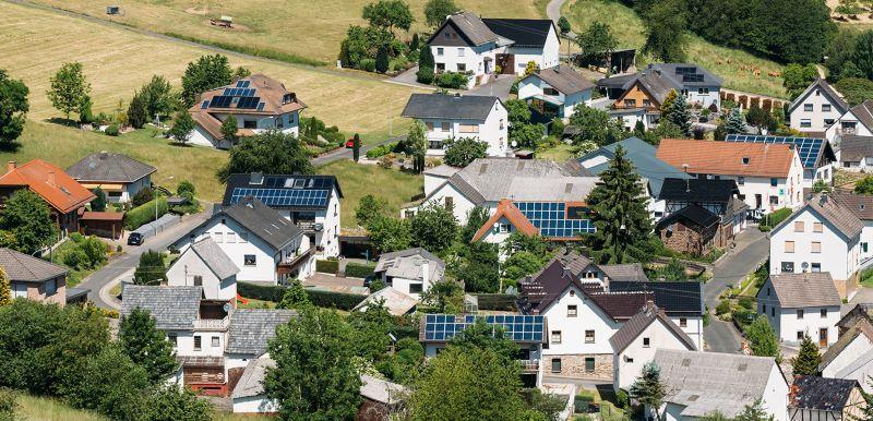 Luftbild zeigt Dorf mit Häusern und PV-Dächern.