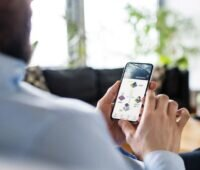 Ein Mann betrachtet sein Mobiltelefon, das eine PV-Appöiaktion anzeigt.