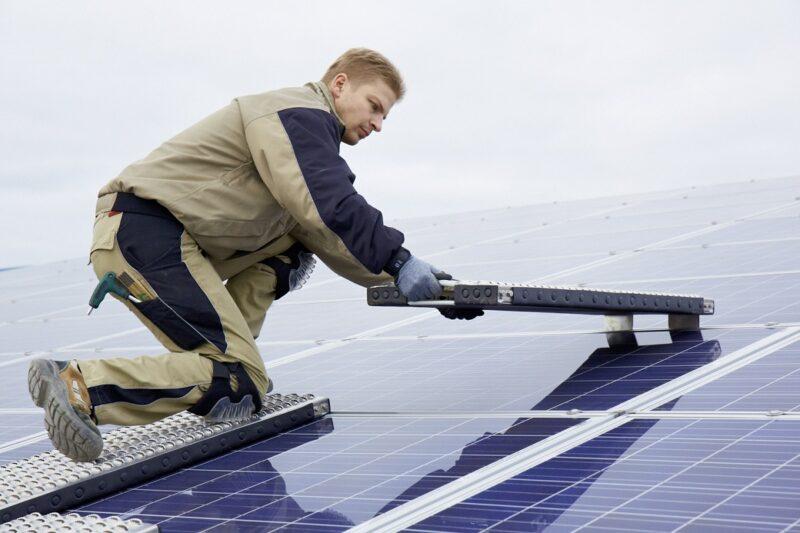 Zu sehen ist ein Monteur. Er verlegt die mobile Photovoltaik-Arbeitsplattform.