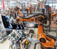 Ein oranger Roboter schwenkt ein Solarmodul in einer Fabrikhalle