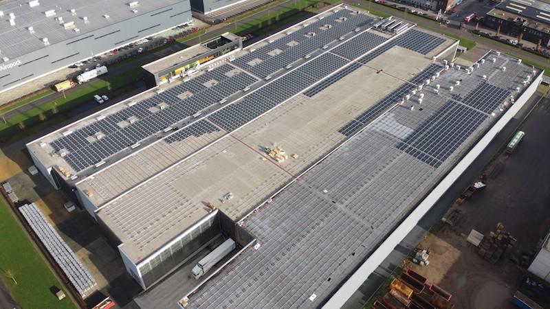 Das Dach eines Gewerbebetriebes wird eine Glas-Glas-Photovoltaikanlage installiert.. Es ist mit Gestellen belegt, auf denen die ersten dunklen Solarmodule installiert wurden.