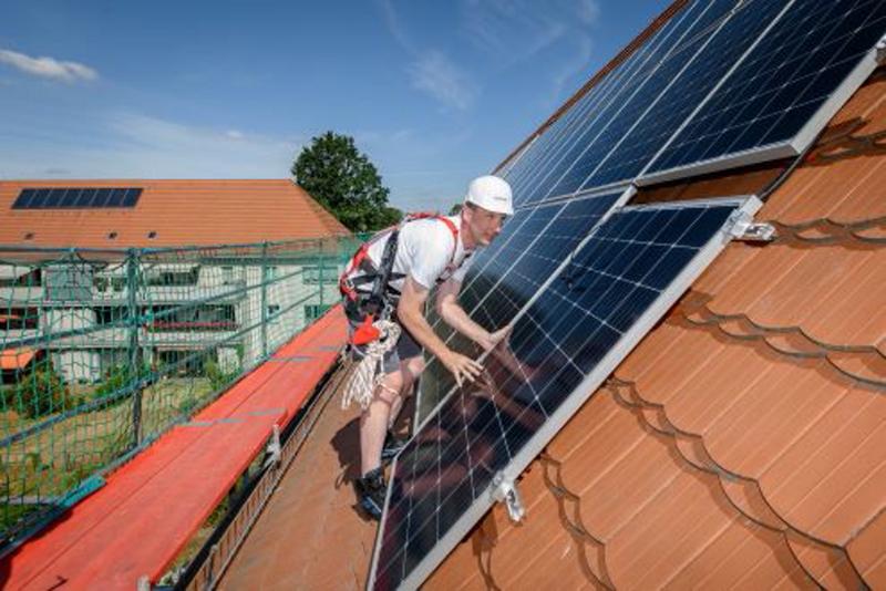 Ein Monteur auf einem Schrägdach installiert Solarmodule.