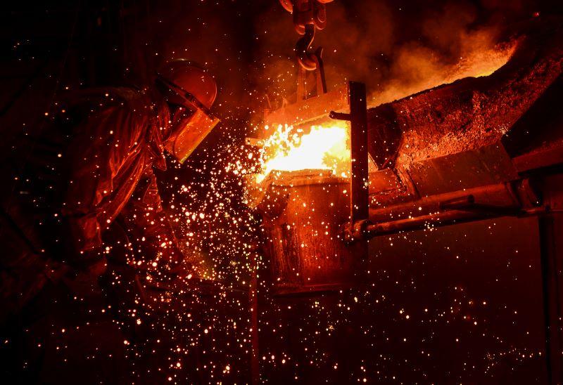 Ein Arbeiter im Schutzanzug bei der Metallschmelze mit glühenden Funken.