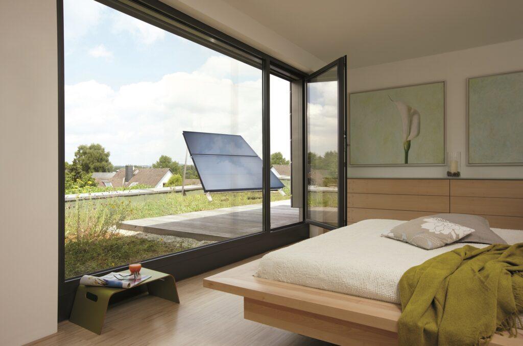 Das Foto zeigt aufgeständerte Sonnenkollektoren auf einem begrünten Flachdach durch eine geöffnete Balkontür.