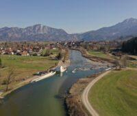 Blick auf einen Fluss mit neuem Wasserkraftwerk vor der Kulisse der Alpen.