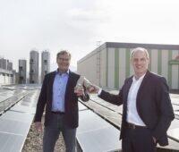 Zu sehen die Geschäftsführer Klaus Preiser von Badenova Wärmeplus und Andreas Schneider von Schwarzwaldmilch die sich zur Fertigstellung der Photovoltaik-Anlage auf dem Dach mit einem Milchprodukt zuprosten.