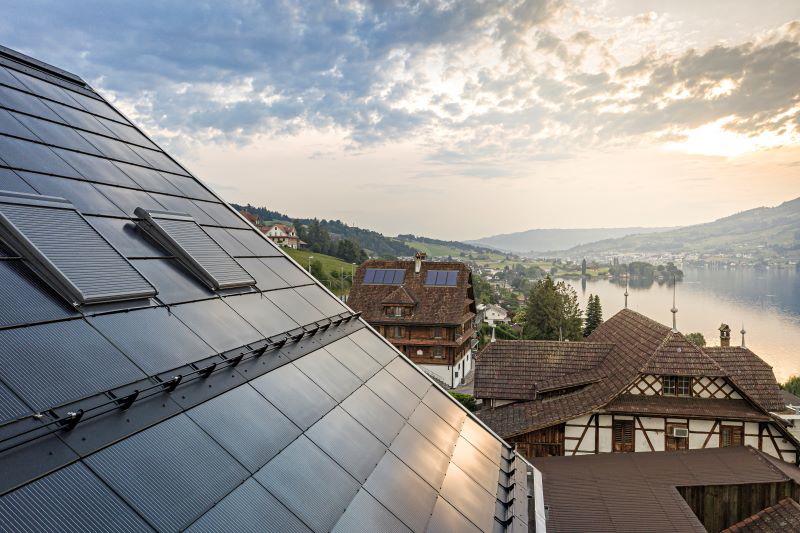 Eine dachintegrierte PV-Anlage in einem Dorf an einem Schweizer Bergsee.