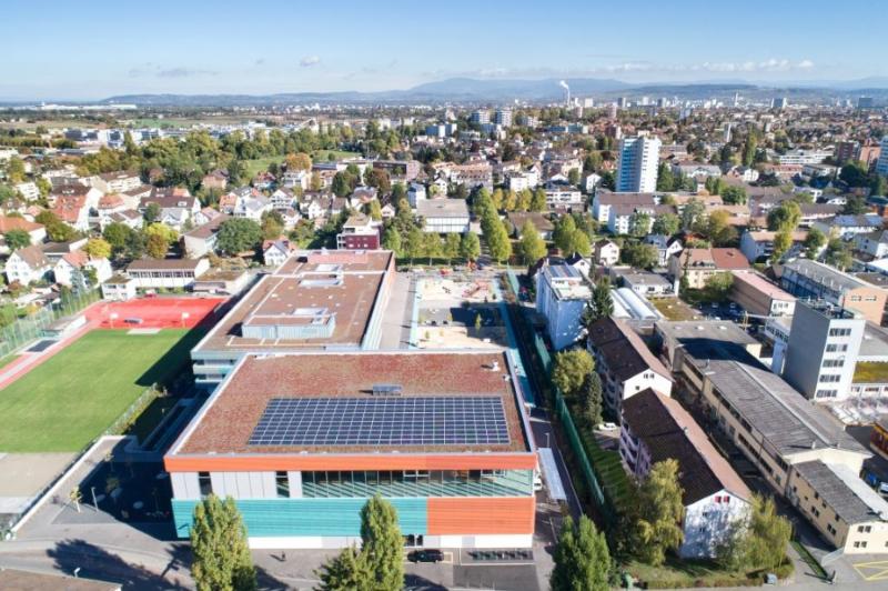 Luftaufnahme des Schweizer Ortes Allschwil. Im Vordergrund eine Schulturnhalle mit einer PV-Anlage auf dem Flachdach.