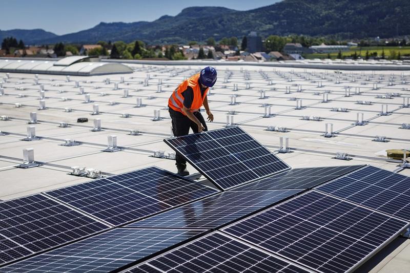 Zu sehen ist ein Arbeiter auf einem Flachdach bei der Montage von PV-Modulen mit dem Photovoltaik-Montagesystem MSP von Schweizer.