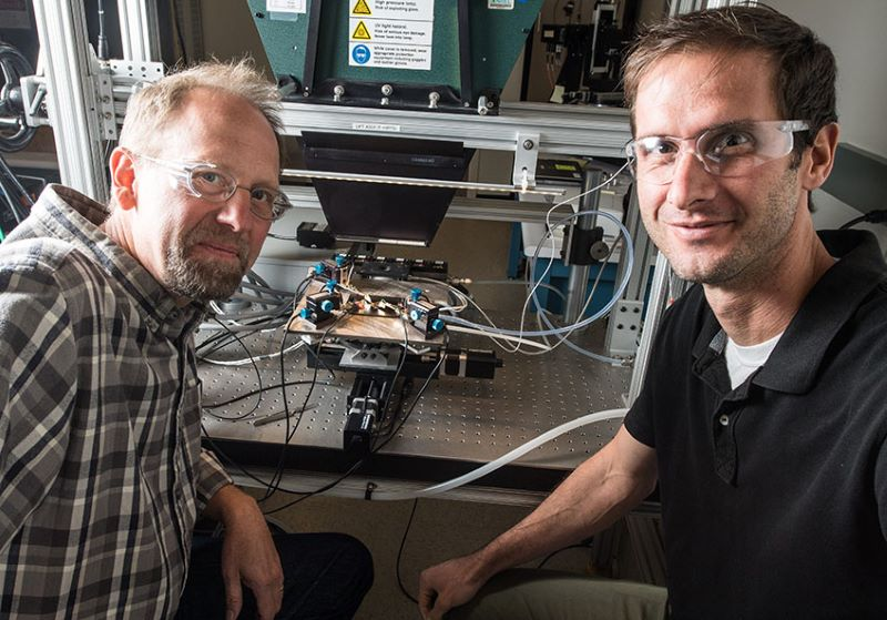 Zwei Forscher sitzen an ihrem labortisch vor einer elektrischen Apparatur.