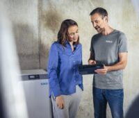 Zu sehen ist ein Installateur der einer Kundin den Stromspeicher erklärt.