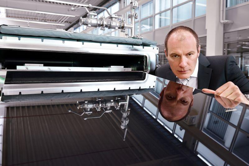 Ein Manager blickt über eine solare Produktionsanlage. Singulus liefert Anlagen für CIGS-Solarmodule