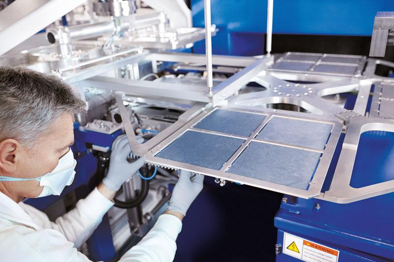 Bild zeigt Maschine zur Produktion von Solarzellen mit Monteur am linken Bildrand