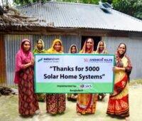Frauen aus Bangladesch vor Haus mit Solarhome-System.