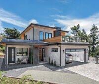 Grafik eines Einfamilienhauses mit Garage, in der ein Energy Management System hängt.