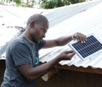 Ein Afrikaner montiert ein Solarmodul vor zwei Hütten mit Wellblechdach.