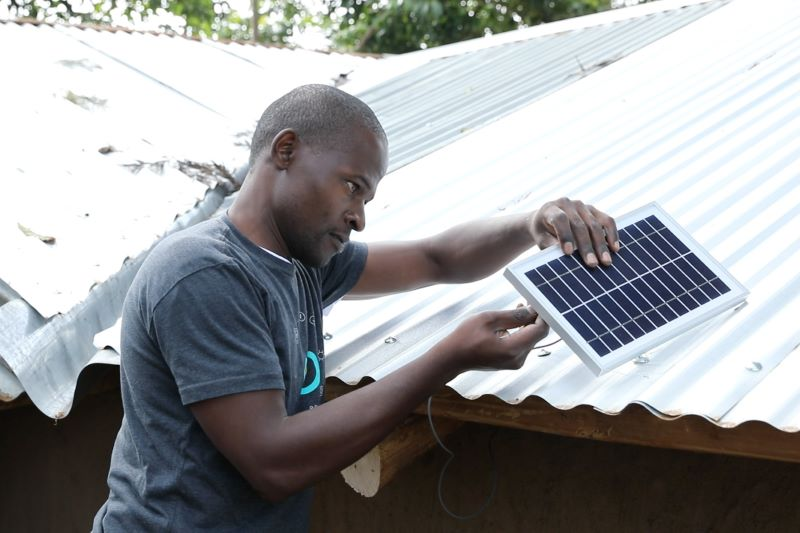 Ein Anwender prüft ein einzelner Solarmodul. Er steht vor Wellblechdächern.