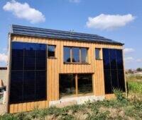 Ein freistehendes Haus, das Solarthermie, PV, Stroh und Holz nutzt.