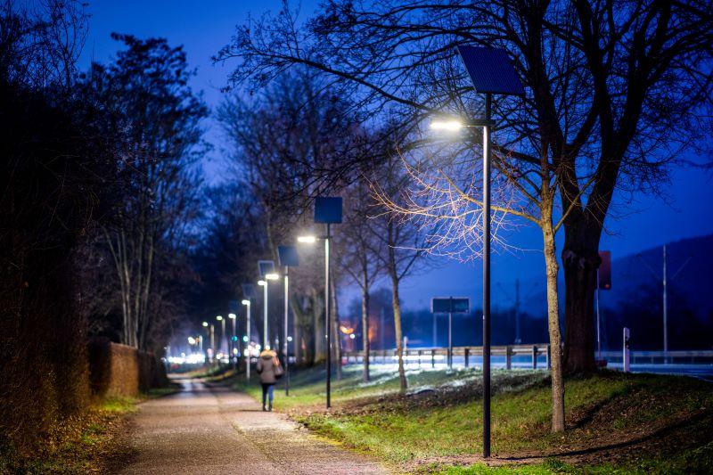 Ein Radweg in der Dämmerung mit Straßenbeleuchtung.