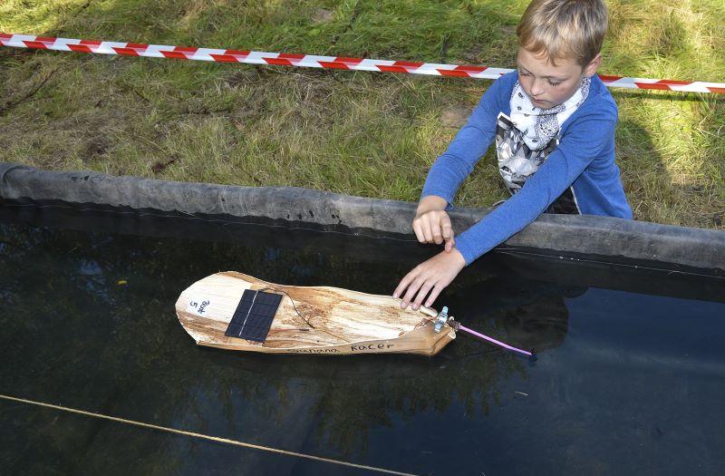 Ein Junge mit einem selbst gebauten Solarboot aus Bananenblättern.