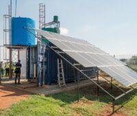Ein Solarpanel vor einem Wellblechcontainer mit Wassertank auf dem Dach.
