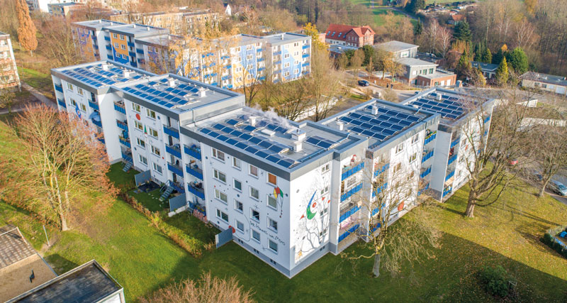 Ein größeres Mehrfamilienhaus auf einer Wiese. Auf dem Photovoltaikanlagen