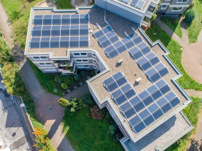 PV-Module auf dem Flachdach einer Wohnsiedlung aus der Vogelperspektive.