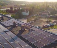 Blick auf ein Flachdach m,it Solarmodulen bei tioefstehender Sonne am Rande eines Wäldchens.
