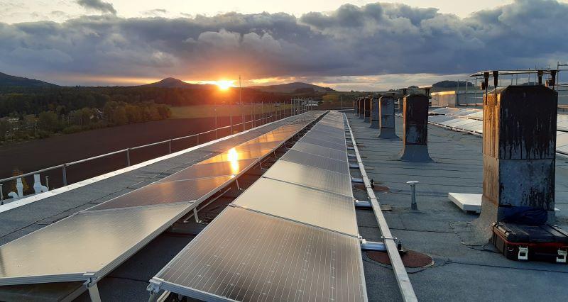 Blick über ein Dach mit Solarmodulen im Abendlicht.