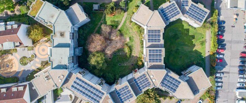 Zu sehen ist die Luftaufnahme einer Mieterstrom-PV-Anlage. Mieterstrom ist ein Baustein die Klimaziele im Gebäudebereich zu erreichen.