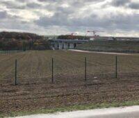 Ein Feld am Rande einer Autobahnbrücke.