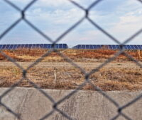 Hinter einem Zaungeflecht ist ein Solarpark in trockener Erde zu sehen. Standort ist das mittelamerikanische Honduras.