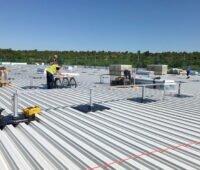 Monteure bauen Gestelle für Solarkollektoren auf Flachdach einer Industriehalle